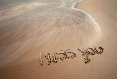 Miss you handwriting. Sign on sea sand with wave. Neutral densitiy filter used to make blurry waves Royalty Free Stock Photo