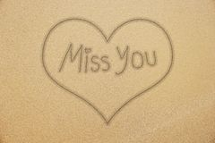 Miss you handwriting with smiling face on sand Royalty Free Stock Photography