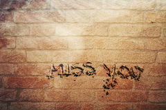 Miss you handwritten on aged wall. Miss you handwriting sign on aged brick wall background. Lovely miss you on texteured wall Royalty Free Stock Image