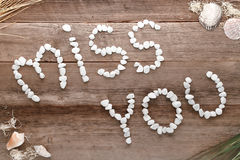 Miss You Love Words Written in Pebbles on Old Wood. The love and feelings sentence miss you in words written in small pebbles letters as a message on old aged Stock Image