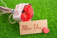 Miss you. In card with heart and bouquet on grass Royalty Free Stock Image