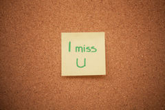 Miss you note on cork board. Note reading `I miss you` on a cork board stock photography