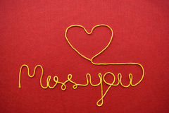 Miss you ribbon greeting and hearts on red background Royalty Free Stock Image