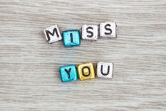 Miss you sign. MISS YOU cube blocks arranged on gray wooden background Stock Image