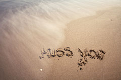 Miss you sign. Miss you handwriting sign on sea sand with wave. Neutral densitiy filter used to make blurry waves Royalty Free Stock Image