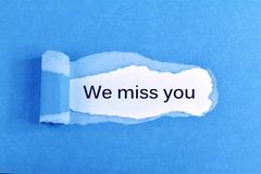 We miss you. Text We miss you appearing behind ripped blue paper Stock Image