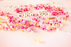 Miss you text beads concept. Miss you text with multicolor beads with pinkish ambient Stock Photo