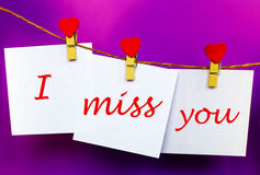 Miss you text on stickers hanging on heart shape pins. Miss you text written at paper stickers hanging on red heart shape wooden pins and pack-thread at purple Royalty Free Stock Photography