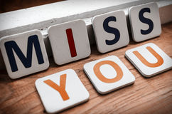 Miss you. Words miss you laid out letters on a wooden background Stock Photography