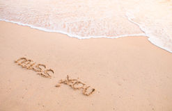 Miss you, words on the sand at beach with wave Royalty Free Stock Image