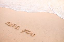 Miss you, words on the sand and moving wave Royalty Free Stock Image