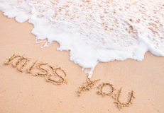 Miss you, words on the sand, touching by moving wave Royalty Free Stock Image
