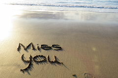 Miss you  written in sand Stock Images