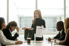 Missbelåten kvinnlig ledare som grälar på anställda för dåligt arbete på royaltyfri bild