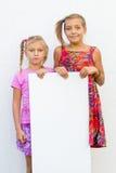 Missbelåtna barnflickor som rymmer papper Royaltyfri Foto