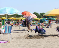 Missbräuchlicher Regenschirmverkäufer auf dem Seestrand mit Regenschirmen Stockbilder