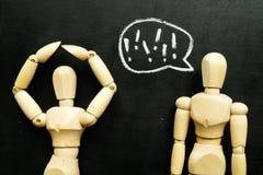 Missbrauch und Einschüchterung in der Kommunikation Zwei hölzerne Figürchen lizenzfreie stockbilder
