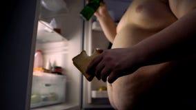 Missbrukat till den feta mannen för snabbmat som äter smörgåsen och dricker öl nära kylen royaltyfria bilder