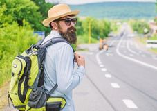 Missed his bus. Tips of experienced traveler. Man bearded hipster tourist at edge of highway. Pick me up. Traveler. Waiting for car take him anyway just to drop royalty free stock photography