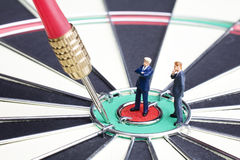 Missed the target. Business figurines placed on a dart board wit a dart stock image