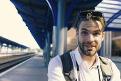Missed train and travelling concept. Guy with sunglasses waits for train, defocused. Young man standing on platform at train station, close up. Tourist with royalty free stock photo
