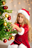 Misser santa die de Kerstmisboom verfraait Stock Foto's