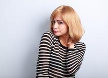 Missfallene misstrauische blonde Frau, die auf Blaurückseite skeptisch schaut Stockfotografie