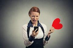 Missfallene Nachrichten der jungen Frau Leseam intelligenten Telefon, das rotes Herz wegwirft lizenzfreies stockbild