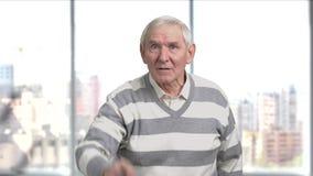 Missfallener älterer Mann, der mit dem Finger gestikuliert stock footage