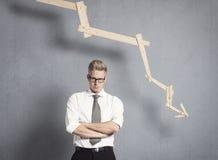 Missfallener Geschäftsmann vor Diagramm mit negativer Tendenz. Stockfotografie