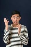 Missfallener junger asiatischer Mann, der mit zwei Händen gestikuliert Lizenzfreies Stockbild