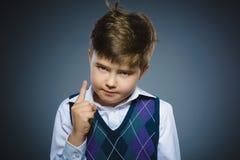 Missfallener verärgerter Junge mit bedroht den Finger, der auf grauem Hintergrund lokalisiert wird Lizenzfreies Stockfoto