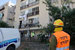 Missile strike on Israel. An israel military rescue team member in front of apartment house with broken windows hit by palestinian missile launched from Gaza Stock Image
