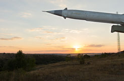 Missile with a warhead on a launcher. At dusk with the sun setting in a golden glow on the horizon royalty free stock photography
