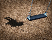 Missing Child. Concept with an empty playground swing and the shadow of a little girl on the park floor as a symbol of children losing their childhood and being