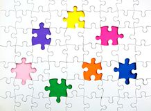 Missing few pieces in a jigsaw puzzle. Missing few white puzzle pieces on the rainbow colours background royalty free stock images