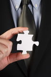 Missing Jigsaw Piece. Man in a business suit holding a single white jigsaw piece Royalty Free Stock Photos