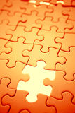 Missing jigsaw piece. Close up of blank orange jigsaw puzzle with single missing piece Stock Photos