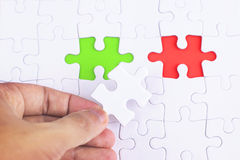 Missing jigsaw puzzle piece with green and red, business concept for completing the final puzzle piece. Stock Photos