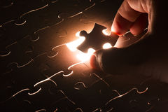 Missing jigsaw puzzle piece with light glow Royalty Free Stock Images