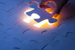 Missing jigsaw puzzle piece with light glow Stock Photography