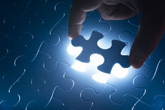 Missing jigsaw puzzle piece with light glow Stock Image