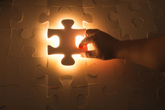 Missing jigsaw puzzle piece with light glow Stock Photos