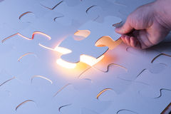 Missing jigsaw puzzle piece with light glow. Business concept for completing the final puzzle piece Stock Photo