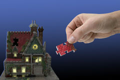 Missing link. House in the evening with hand and puzzle-piece Royalty Free Stock Photos