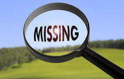 Missing. Magnifying glass with the word missing on blurred nature background. Searching missing concept Stock Images