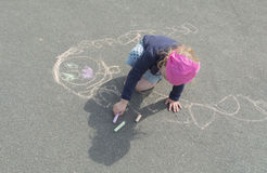 Missing mother on the pavement draws a fine baby girl. The baby girl draws on the pavement with crayons thinking about mom Stock Photo