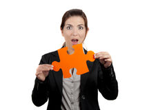 The missing piece. Business woman with a astonish expression, holding a big piece of puzzle, isolated on white Royalty Free Stock Images