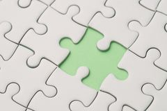 Missing piece for business success strategy metaphor concept. Closed up of white jigsaw puzzle missing only one piece on pastel green background Royalty Free Stock Photo