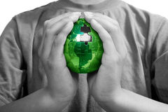 The Missing Piece, Green Energy. Earth puzzle, held by a young boy looking for solution Stock Photo
